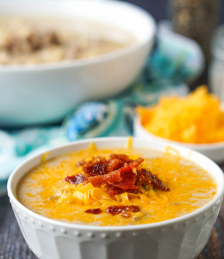 closeup of a bowl of low carb cheeseburger soup with melted cheddar cheese and bacon