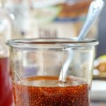 glass of Thai tea chia seed drink with jars in background and text