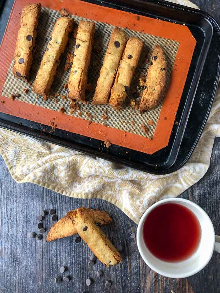 cookie sheet with chocolate chip keto biscotti and a few pieces with a cup of tea and scattered chocolate chips