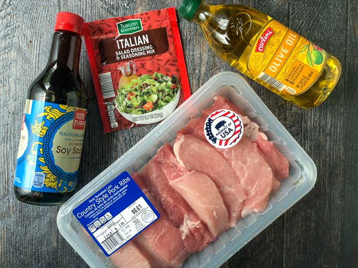 Ingredients to make air fryer pork kebabs: soy sauce, Italian dressing packet, olive oil and country style pork ribs