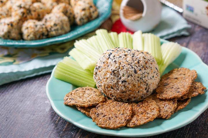 a salmon & cream cheese ball rolled in everything bagel spice on a blue plate with celery sticks and keto crackers