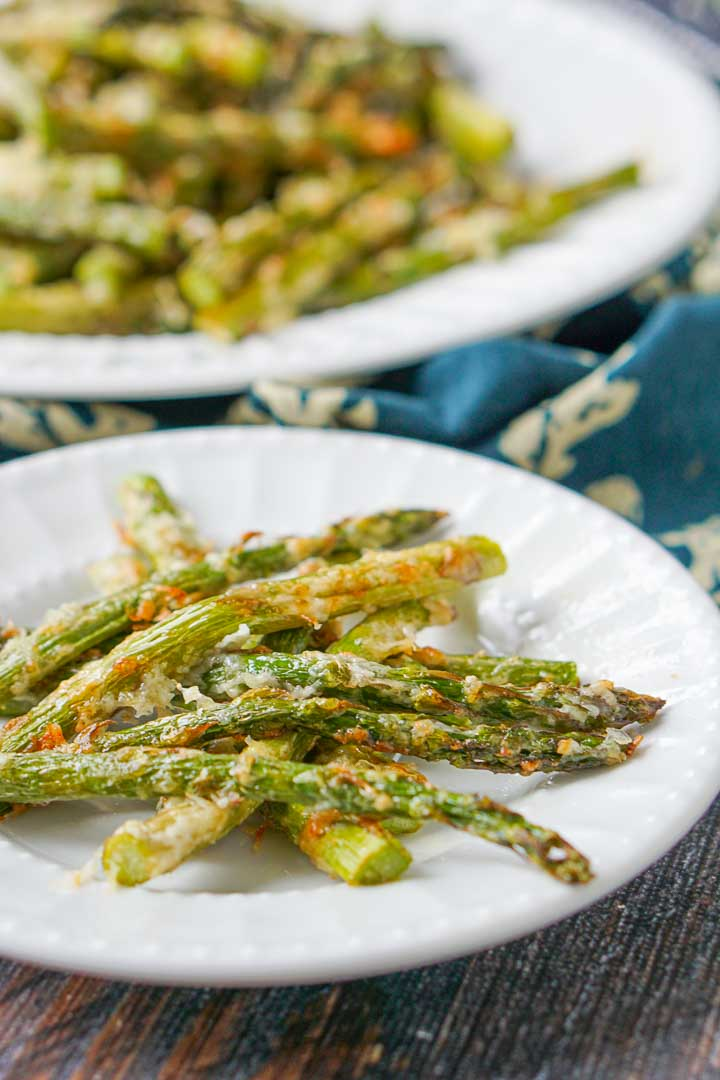 close up of a white plate with low carb asiago asparagus fries  and another plate in the background