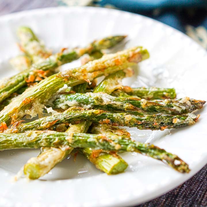 close up of a white plate with low carb asiago asparagus fries made in the air fryer