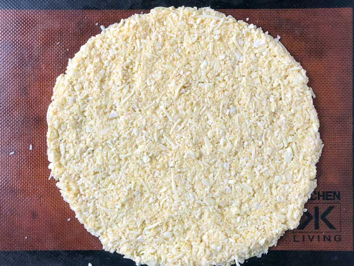 raw cauliflower crust pizza on silicone mat