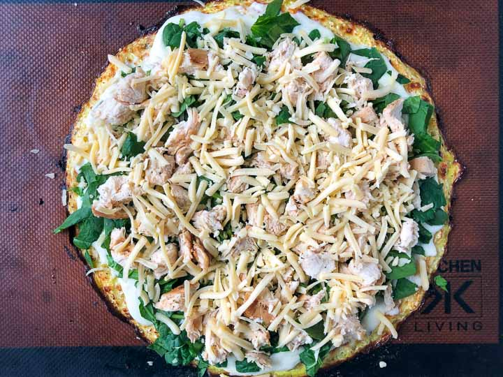 cooked cauliflower crust with all the fixings ready to go back in the oven