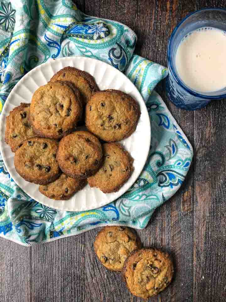 white plate full of  keto chocolate chip cookies with blue paisley tea towel and blue glass of milk