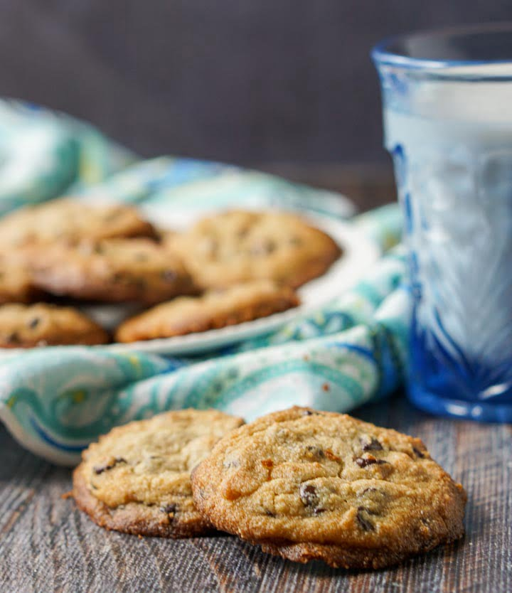 closeup of keto chocolate chip cookies with a plate in the background along with a blue glass of milk
