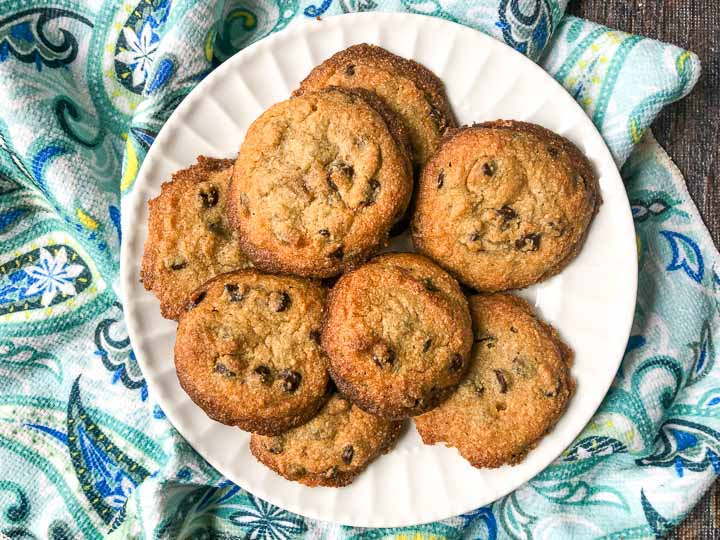 white plate with baked keto chocolate chip cookies with a colorful blue tea towel underneath