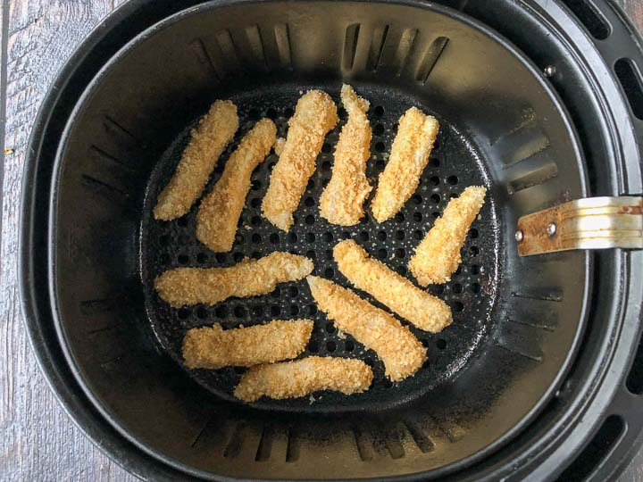 keto fish sticks in the basket of an air fryer ready to be baked