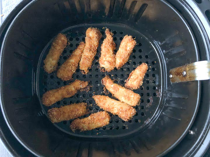 keto fish sticks in the basket of an air fryer that are baked