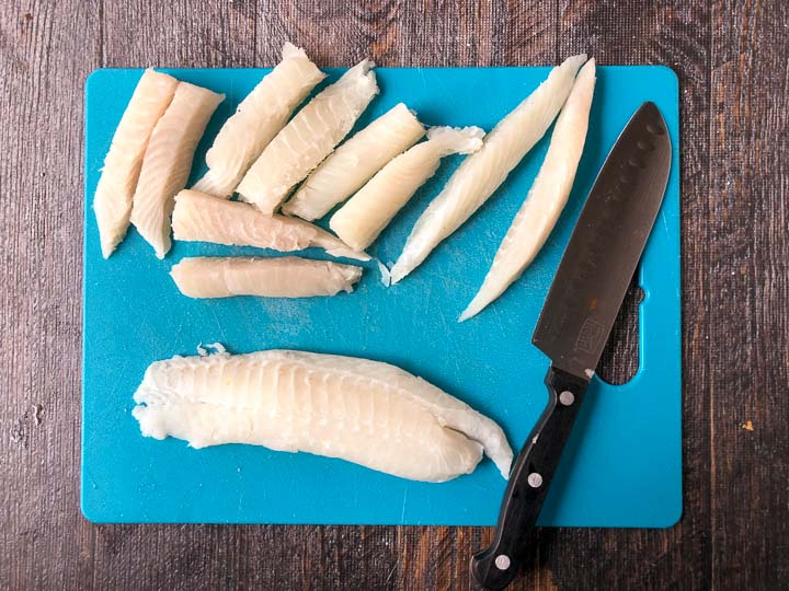 blue cutting board and knife is tilapia loins cut into fish sticks