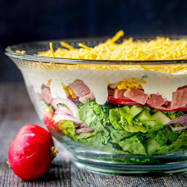 glass bowl with low carb layered ham salad and 2 raw radishes