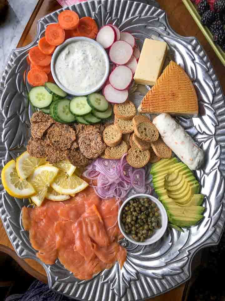 silver metal platter with lox, avocado, red onion, capers, low carb crackers, cheeses, dip and raw vegetables
