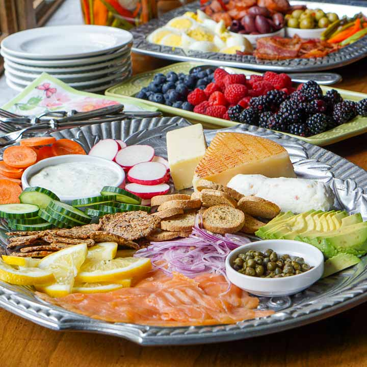 silver metal platter with low carb brunch foods, fresh berries and white plates in the background