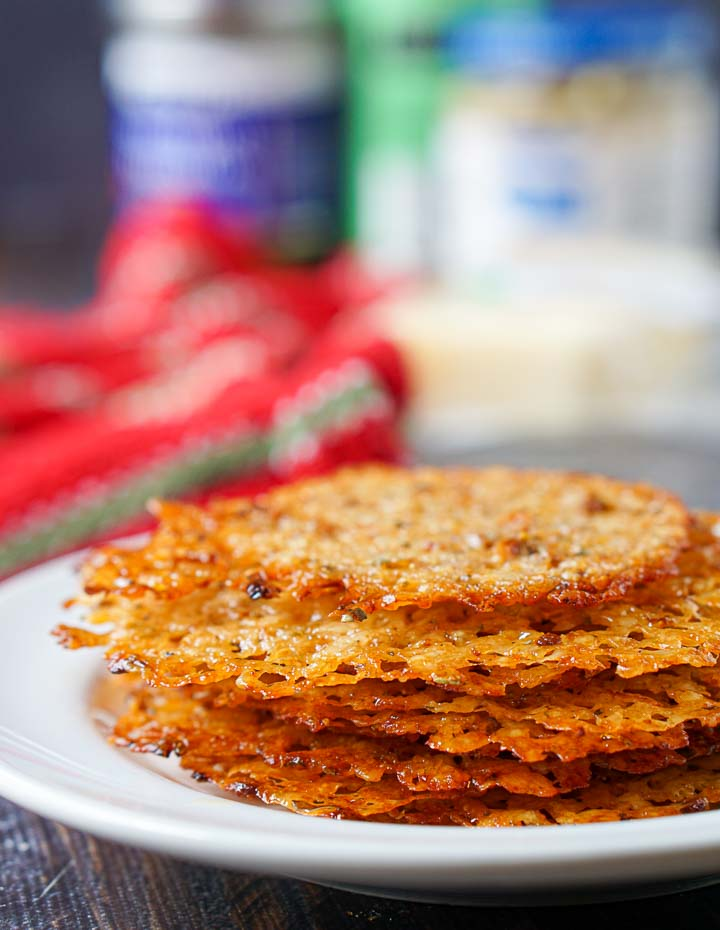 cheese crisps stacked on a white plate with ingredients and red towel in background