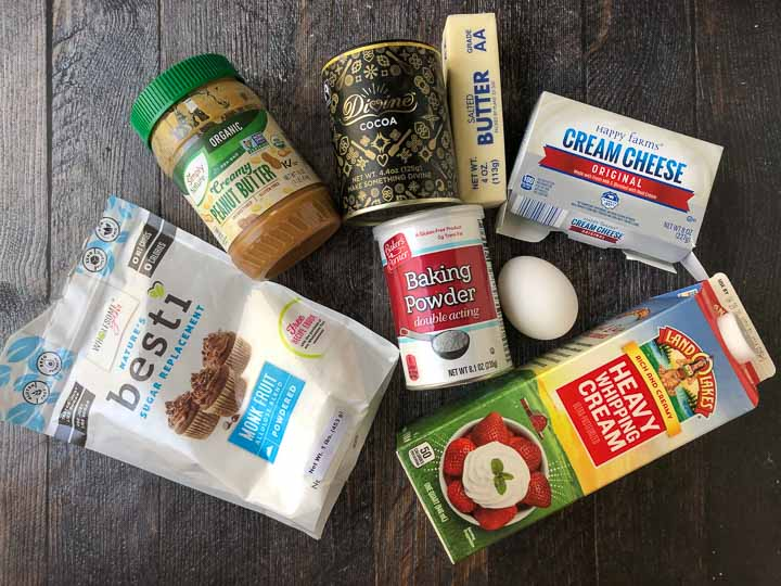 ingredients to make microwave keto cups: peanut butter, sweetener, cocoa powder, baking powder,  butter, cream cheese, eggs and heavy cream