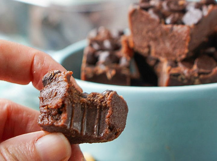 fingers holding a piece of low carb fudge with a bite taken out