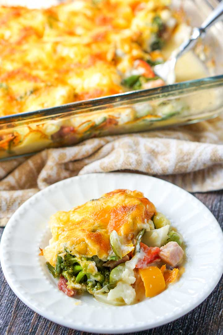 white plate with low carb creamy vegetable & ham casserole with baking dish in the background