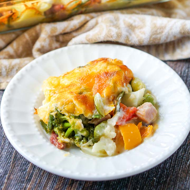 white plate with low carb creamy vegetable & ham casserole