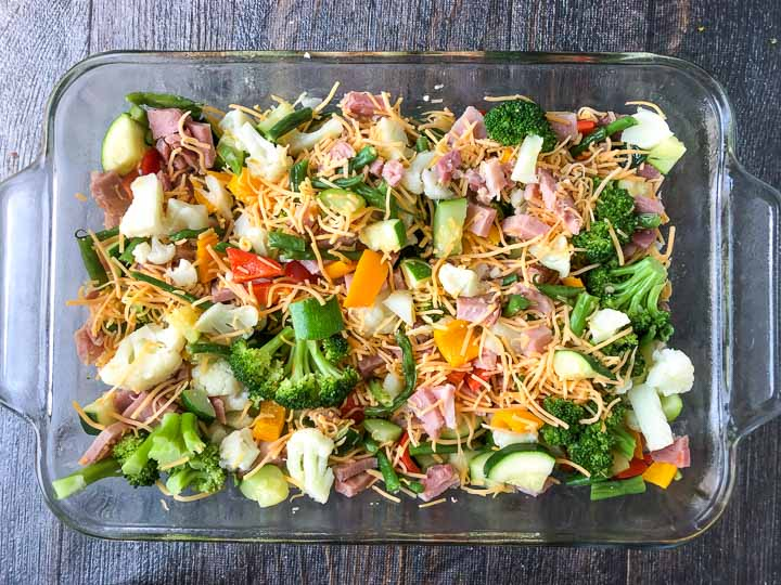 glass baking dish with cooked vegetables, ham and cheese ready to be baked