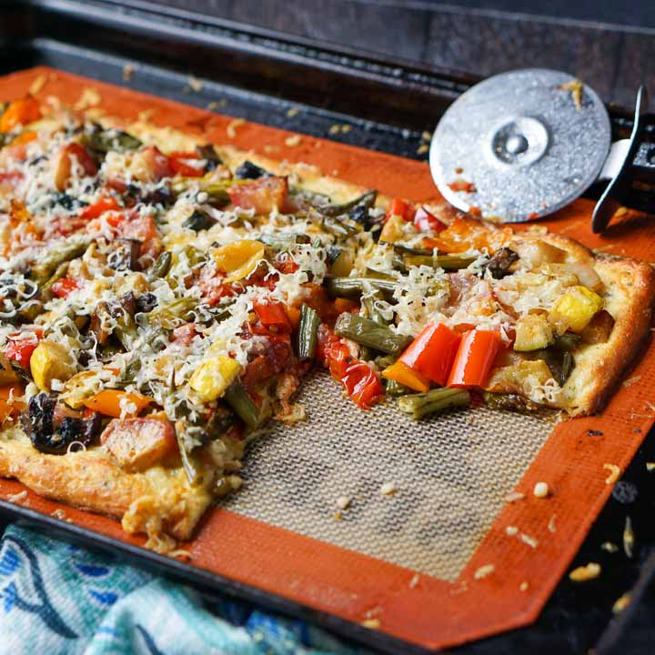 cookie sheet with low carb roasted vegetables flatbread pizza with a pizza cutter