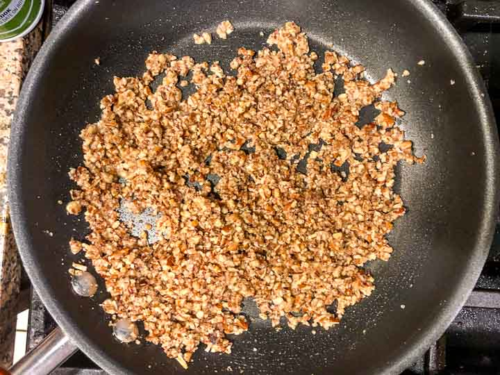 skillet with crushed butter pecans that have been toasted