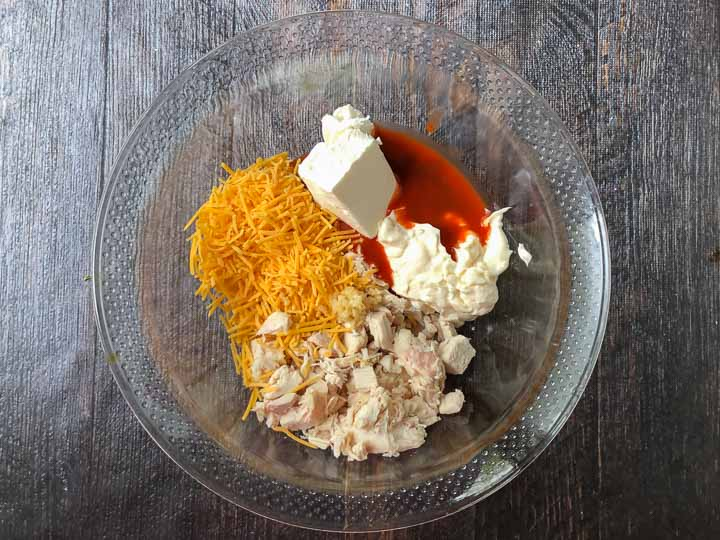 ingredients to make keto buffalo chicken dip in glass bowl : cheddar cheese, chicken, mayo, cream cheese, garlic and hot sauce