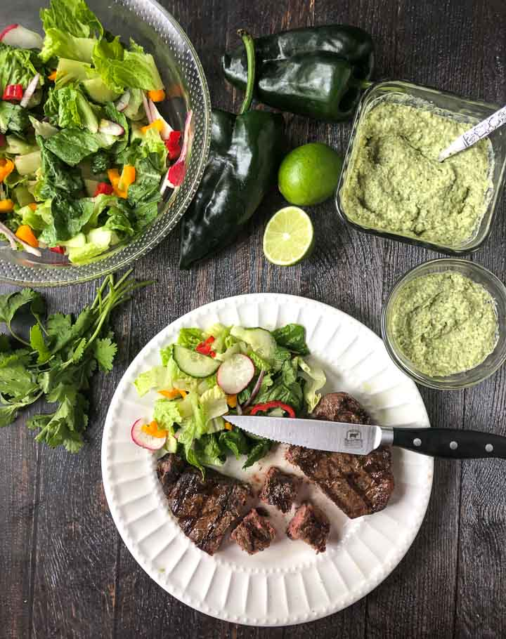 white plate with a cut up steak and a garden salad, fresh limes, fresh poblano peppers, cilantro and a jar of creamy grilled poblano sauce