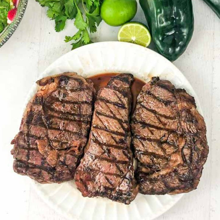 grilled steaks on a white plate with limes, cilantro and poblanos at the top of the plate