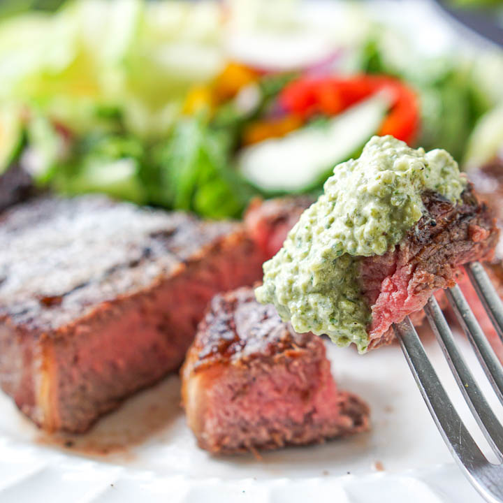 closeup of a piece of steak on a fork dipped in a creamy grilled poblano sauce with the rest of the steak in the background