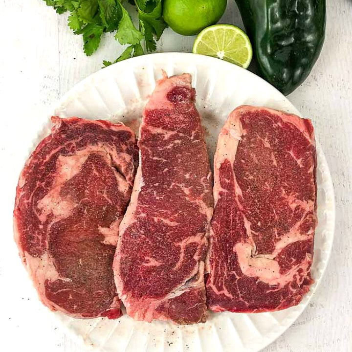 raw steaks on a white plate with limes, poblanos and cilantro nearby