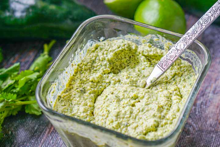 glass square jar with the creamy poblano sauce and fresh cilantro, limes and poblanos surrounding