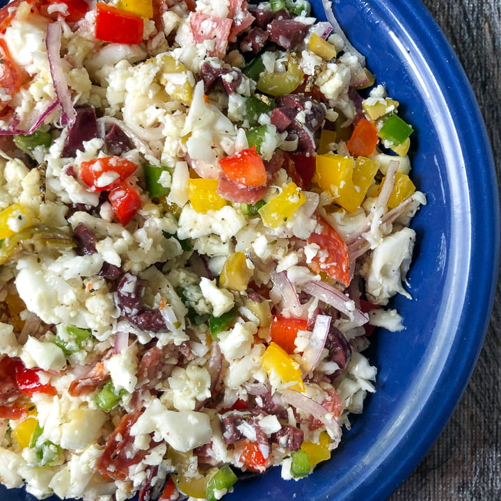 closeup of a bright blue bowl with low carb antipasto cauliflower rice salad