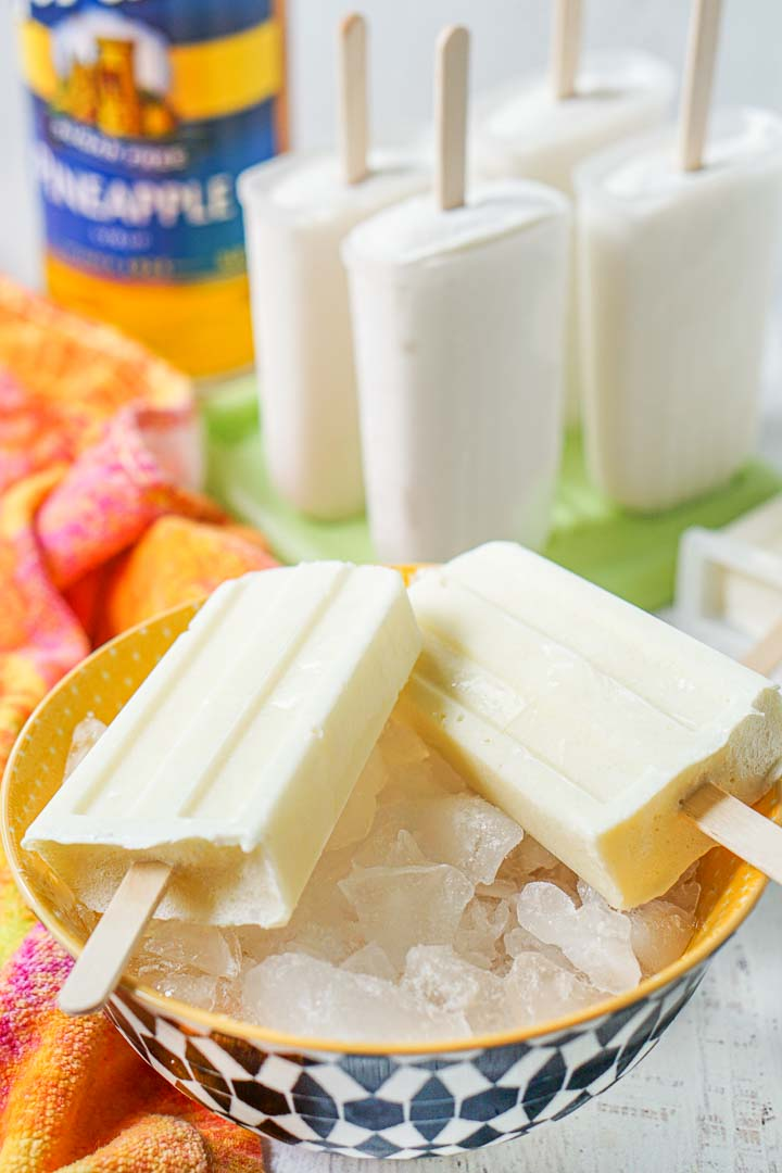 closeup of yellow bowl with ice and sugar free pina colada pops with other popsicles in the background and a bottle of Torani syrup