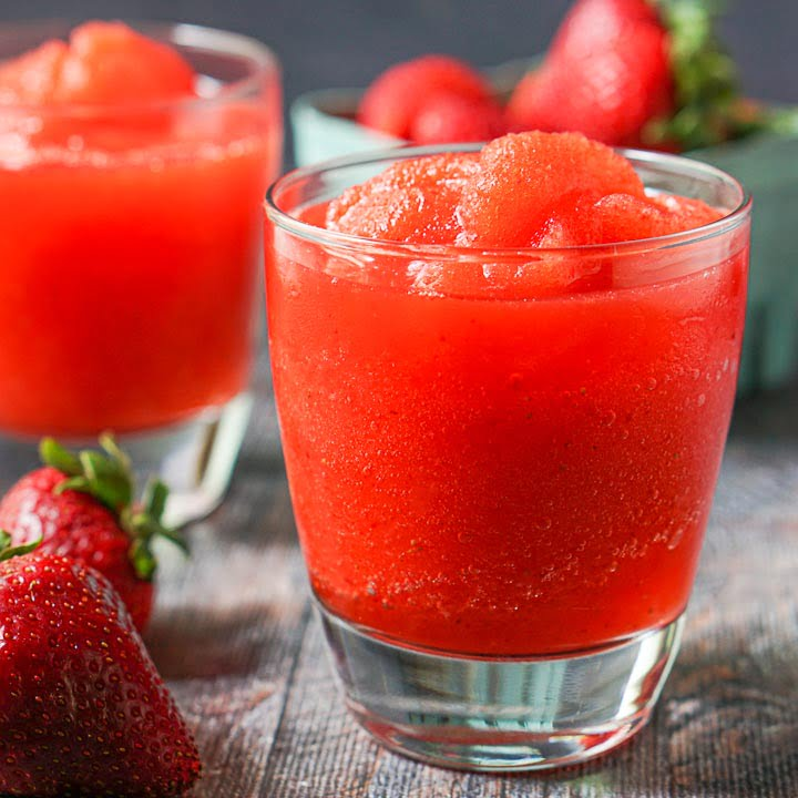 2 glasses filled with keto strawberry margarita slush with a raw strawberries in the background