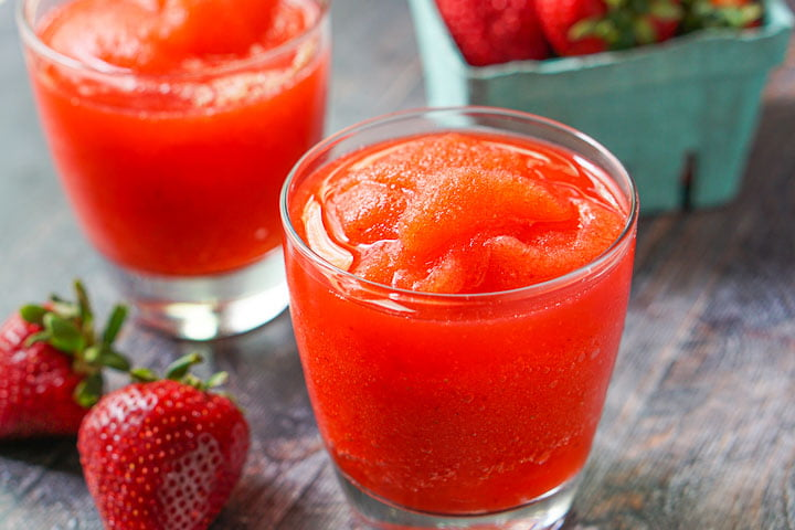 closeup of glasses filled with low carb strawberry margarita slush with a raw strawberries in the foreground