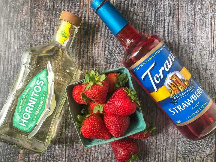 ingredients for sugar free strawberry margaritas: tequila, strawberries and Torani sugar free strawberry syrups