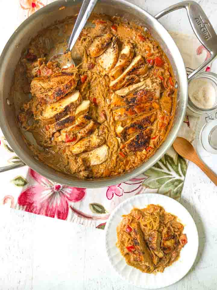 skillet and white plate with low carb cajun chicken spaghetti squash dinner on floral napkin