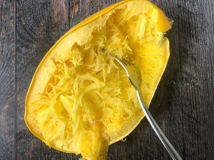 half of a cooked spaghetti squash with a fork scraping the middle to look like noodles
