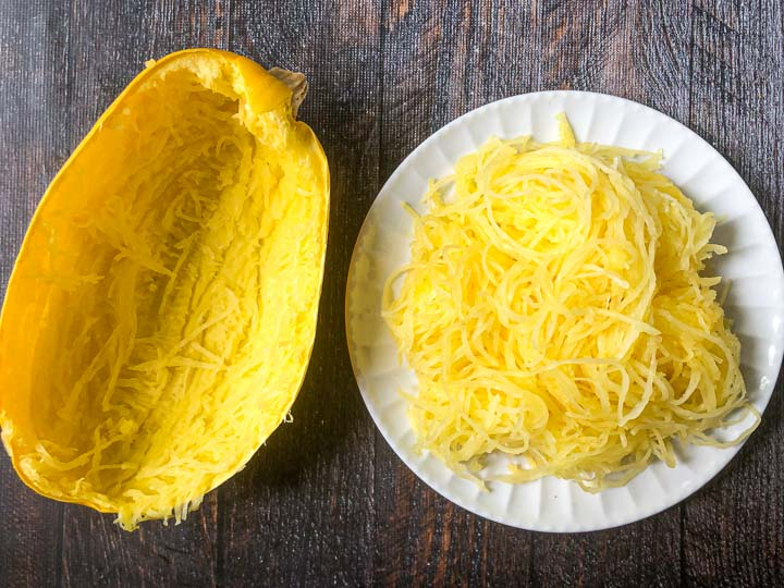 white plate with cooked spaghetti squash next to an empty half of a spaghetti squash