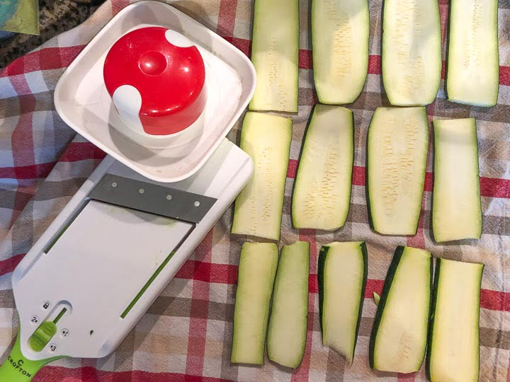 mandoline and raw sliced zucchini on a checked tea towel