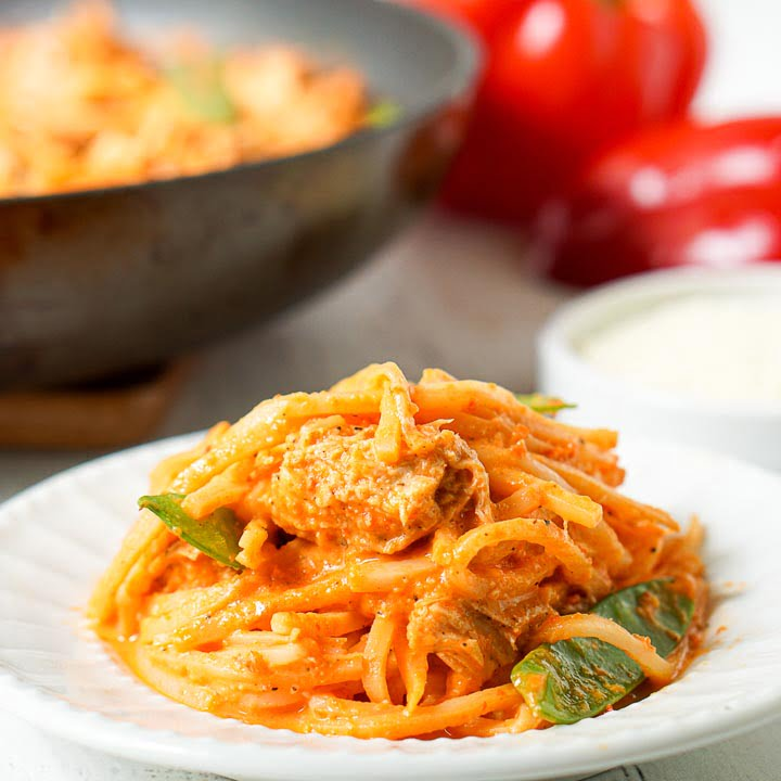 closeup white plate with low carb creamy red pepper pasta and pan and red peppers in the background