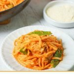 white plate and pan with low carb creamy red pepper pasta with text