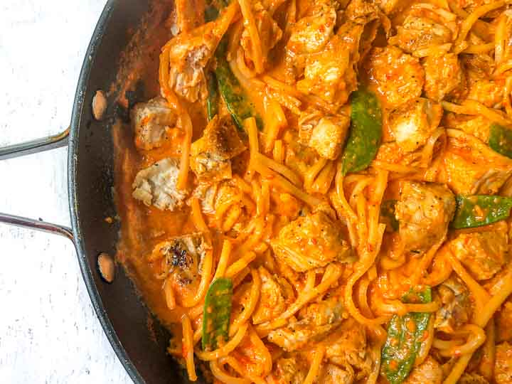 closeup of a pan filled with low carb creamy red pepper pasta with chicken and snow peas