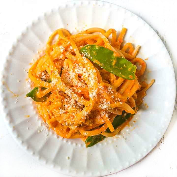white plate with low carb creamy red pepper pasta with chicken and snow peas
