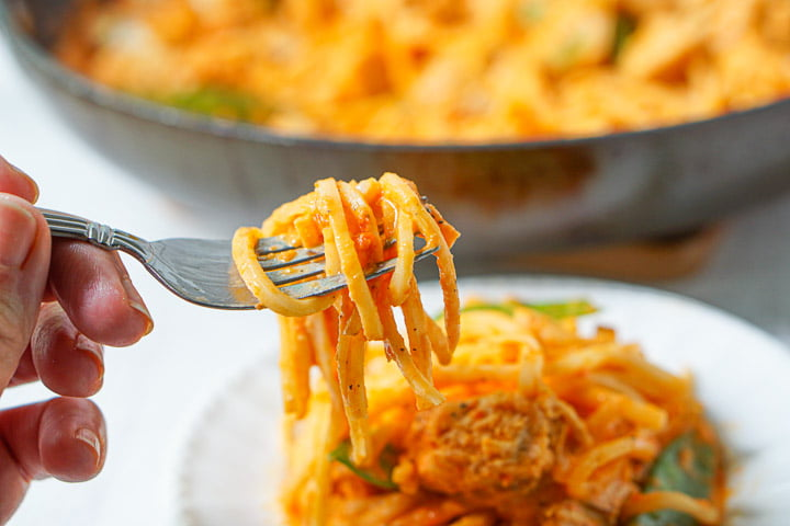 a forkful of palmini linguine with the red pepper sauce