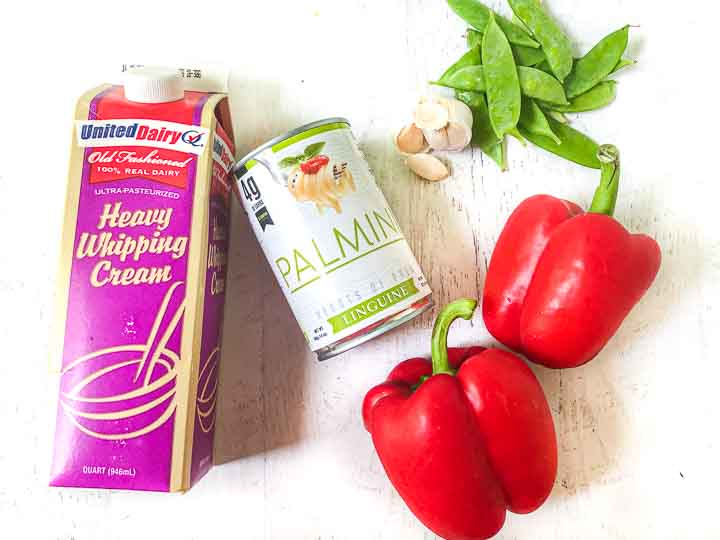 ingredients to make the keto red pepper sauce and pasta: heavy cream, red bell peppers, garlic cloves, snow peas and a can of palmini