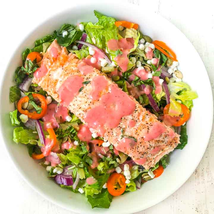 big white bowl with colorful goat cheese & salmon salad with raspberry vinaigrette
