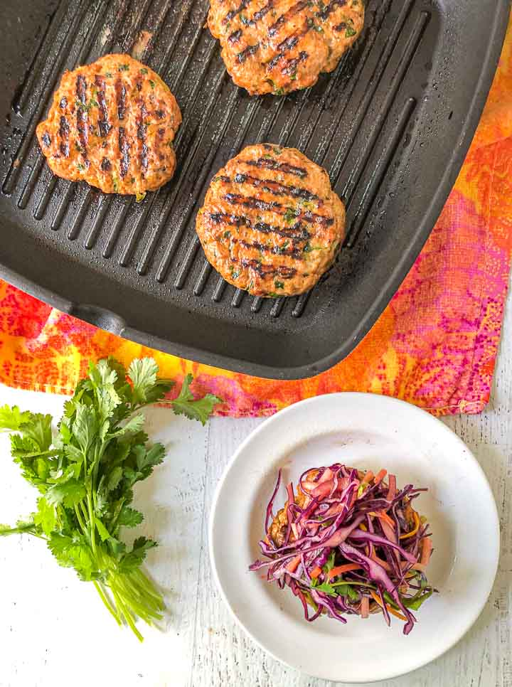 grill pan and white plate with Thai turkey burgers and a bunch of cilantro and a colorful towel underneath