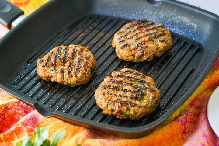 grill pan with 3 turkey burgers on a colorful orange and pink towel